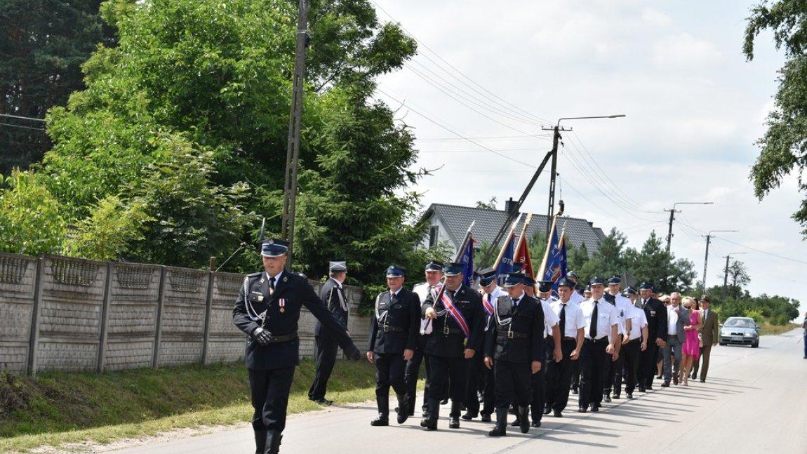 Przemarsz gminnych jednostek OSP z zaproszonymi gośćmi, mieszkańcami do Kaplicy w Zychorzynie.