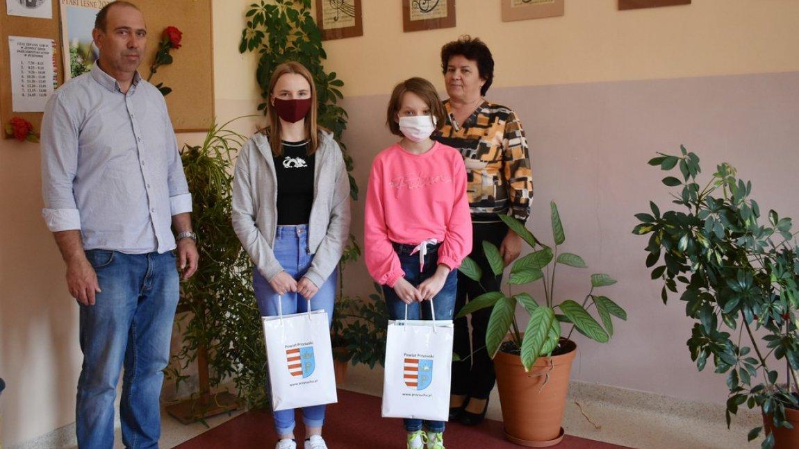 Zdjęcie przedstawia dyrekcję Publicznej Szkoły Podstawowej im. Jana Kochanowskiego w Rusinowie oraz laureatki konkursu